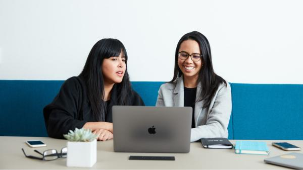 Two women colleagues sitting in front of a Mac laptop: one woman on the left with a black shirt, and another woman on the right with glasses and a gray blazer