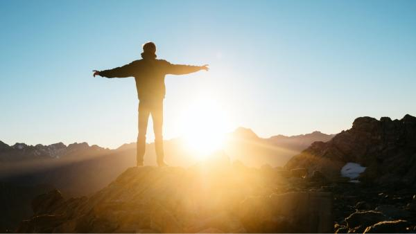 A figure at the top of a mountain with their arms outstretched to either side, facing the rising sun