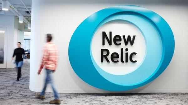 At the New Relic office, a large logo displayed on the wall and people walking around the corridor