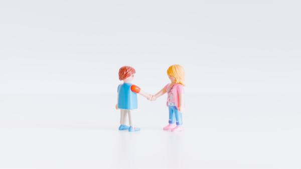 Two miniature doll-type figures shaking hands